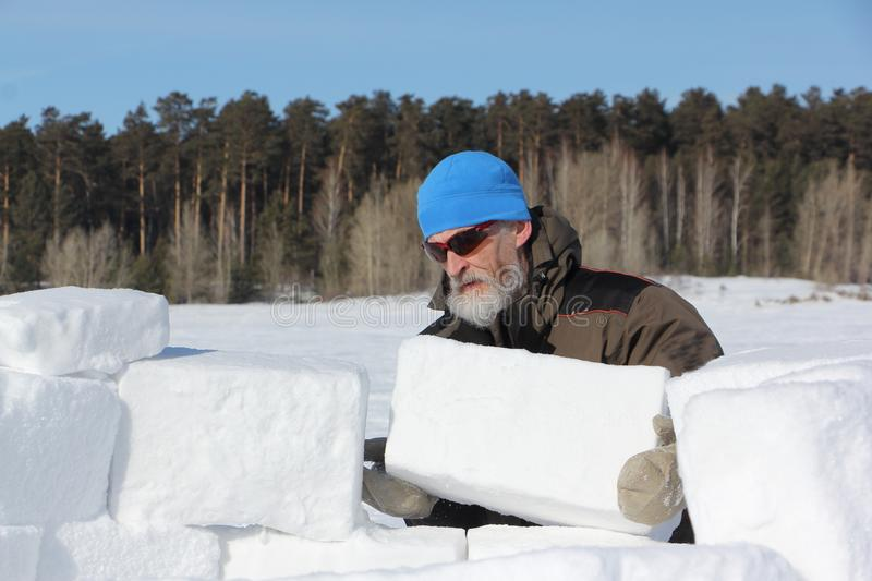 Man in a blue hat and sunglasses building an igloo from snow blocks in winter royalty free stock photo