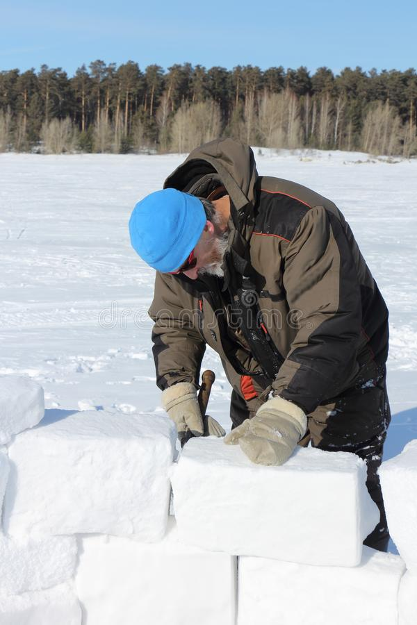 Man in a blue hat and sunglasses building an igloo from snow blocks in winter royalty free stock photography