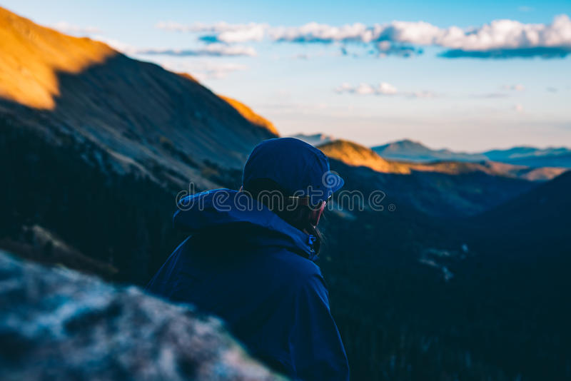 Download Man In Blue Hoodie Standing On Mountain Cliff During Daytime Stock Photo - Image of mountains, photo: 83036058
