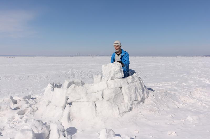 Man in a blue jacket building an igloo on a glade stock photos