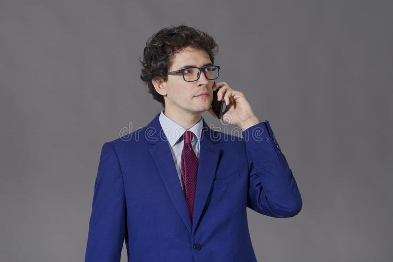 Curly man in blue jacket talking by phone royalty free stock image
