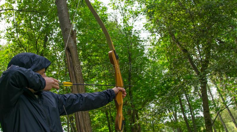 A man in a blue jacket, pulls the bowstring, to hit the target, against the green forest royalty free stock photography