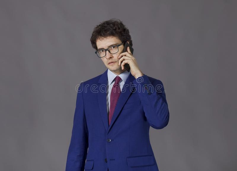 Man in blue jacket talking by mobile phone royalty free stock photography