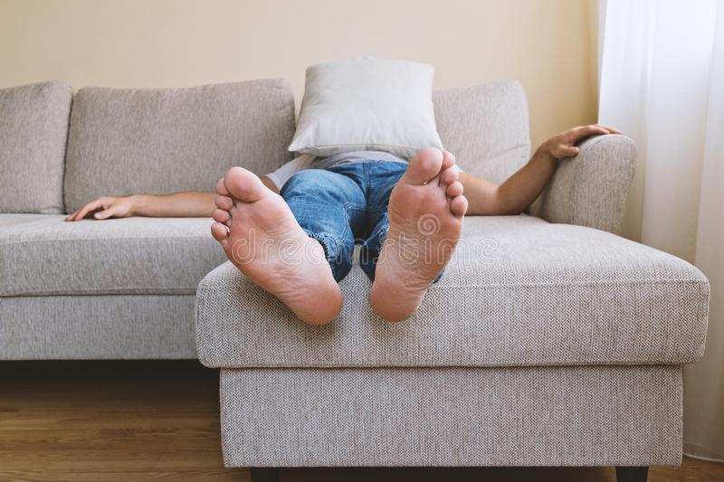 Man in blue jeans lying on sofa in depression. Faceless adult tired man in blue jogger jeans lying on beige sofa in depression. Men`s depression concept stock images