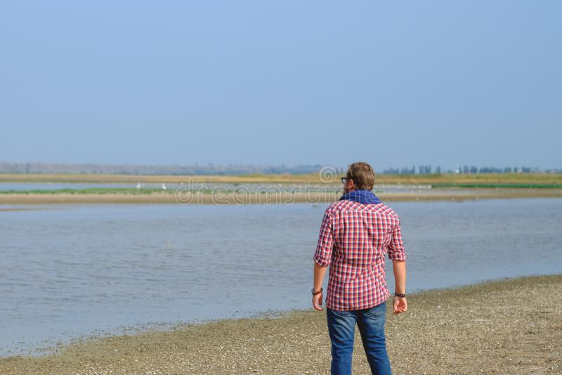 A man in blue jeans and a red shirt walking the river royalty free stock photos