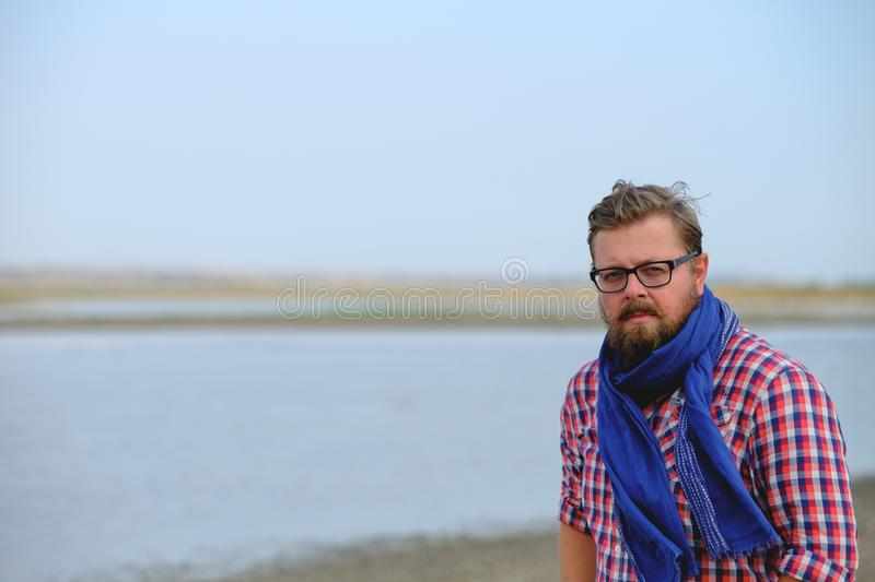 A man in blue jeans and a red shirt walking the river royalty free stock photo