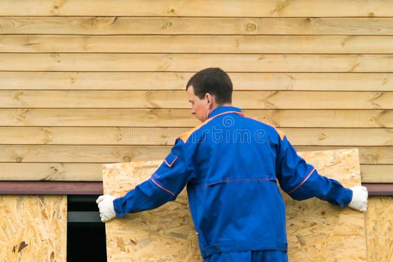 A man in a blue jumpsuit closes the bottom of the house with a wooden shield royalty free stock image