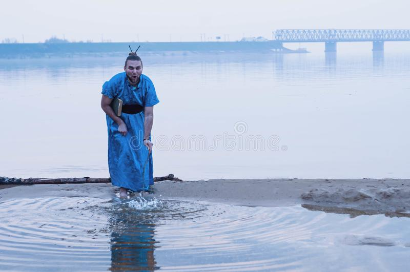 Bearded man in blue kimono holding book, standing on river bank and splashing water with wooden stick stock photography