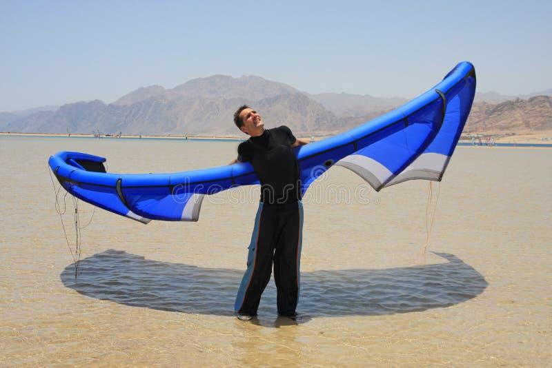 Man with blue kite royalty free stock image