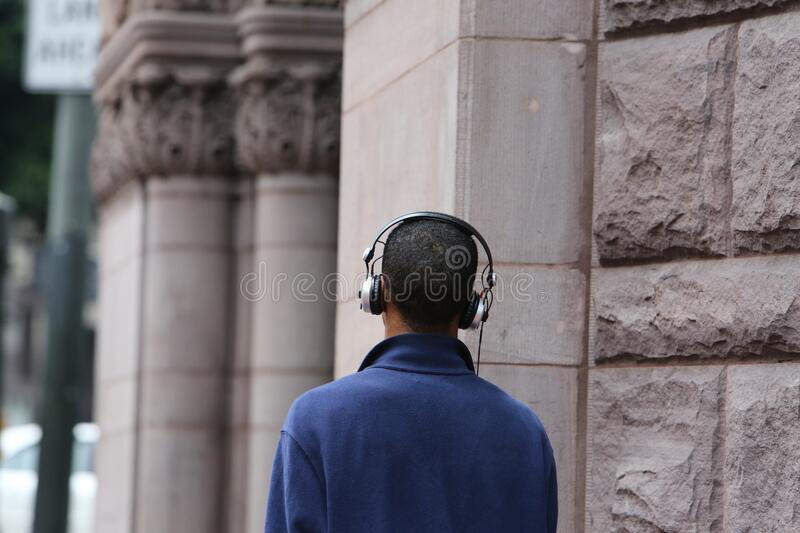 Man in Blue Long Sleeve Coat Wearing Silver and Black Headphones during Daytime stock images