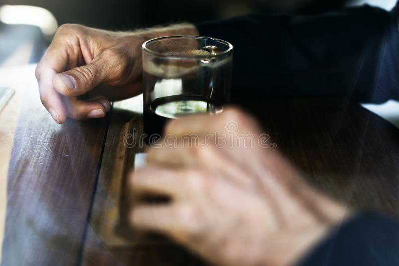 Man in Blue Long Sleeve Shirt In Front Of Drinking Glass On Brown Wooden Table stock photography