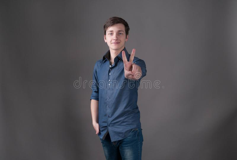 man in blue looking at camera and showing victory symbol with hand on grey background with copy space royalty free stock images