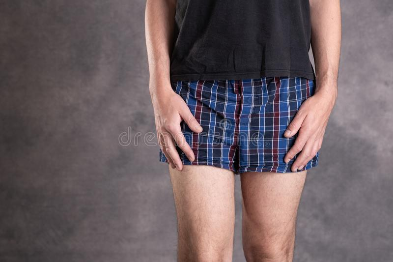 Man in blue plaid boxer shorts. In front of gray background royalty free stock photo