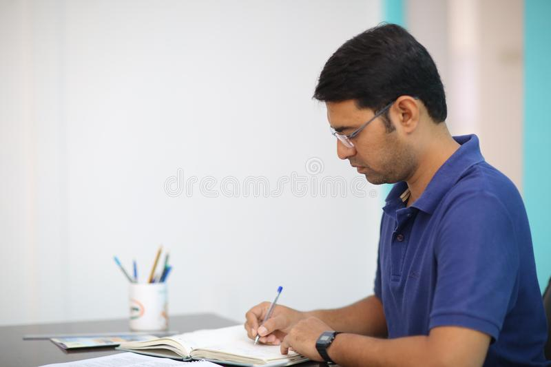 Man in Blue Polo Shirt Writing stock photo