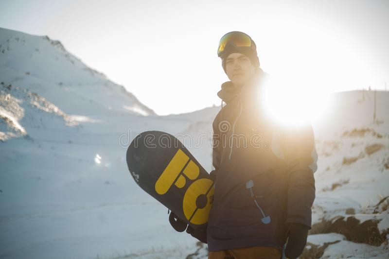 Man in Blue Pullover Hoodie Holding Blue and Yellow Snowboard stock photo