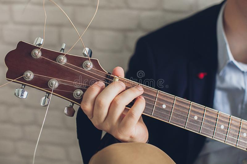 A man in a blue shirt and a dark blue jacket plays guitar against a light brick wall. Concepts Hobbies and interests in music. The stock photos