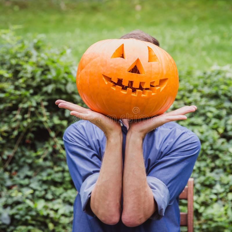 Man in blue shirt holding big pumpkin in front of his face. Happy Halloween. Man in blue shirt holding big pumpkin in front of his face outside. Happy Halloween stock photo