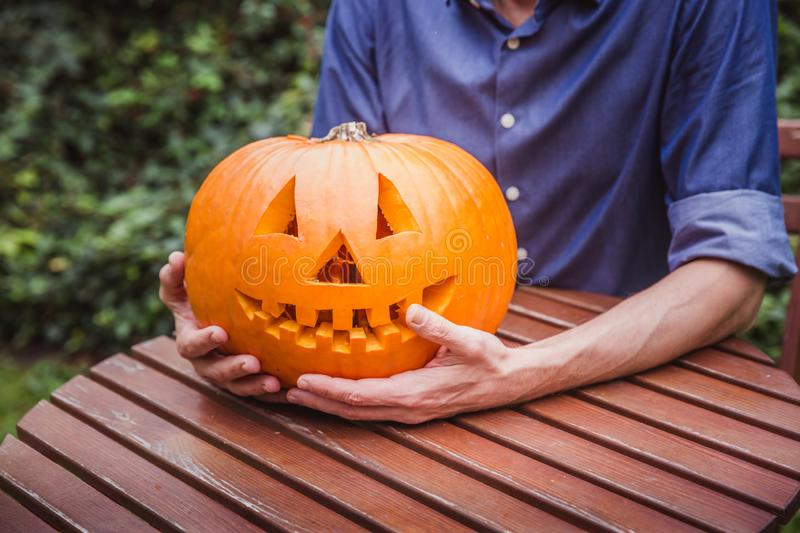 Man in blue shirt holding big pumpkin in front of his face. Happy Halloween. Man in blue shirt holding big pumpkin in front of his face outside. Happy Halloween royalty free stock photos
