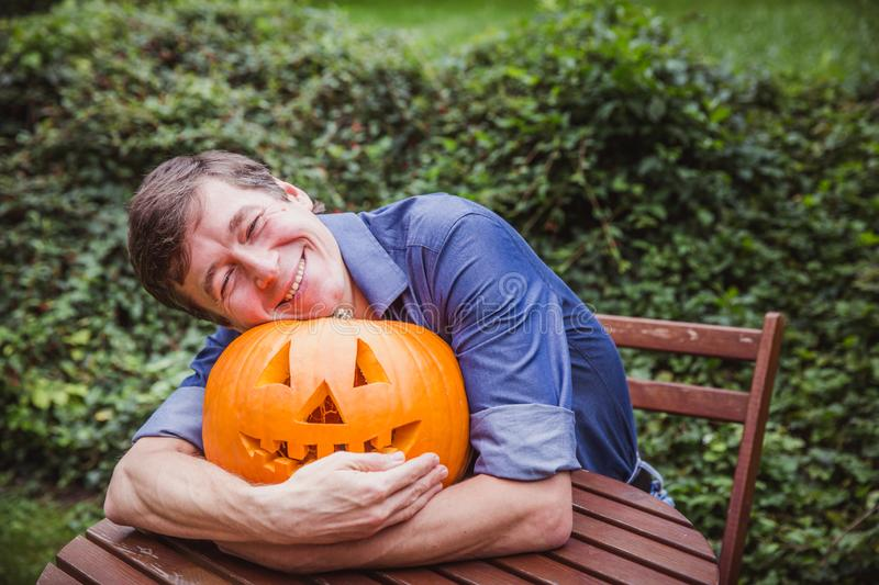 Man in blue shirt holding big pumpkin in front of his face. Happy Halloween. Man in blue shirt holding big pumpkin in front of his face outside. Happy Halloween stock photos