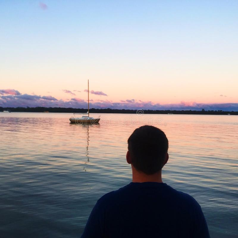 Man in Blue Shirt Near Blue Sea and White Boat Under Blue Sky stock photo