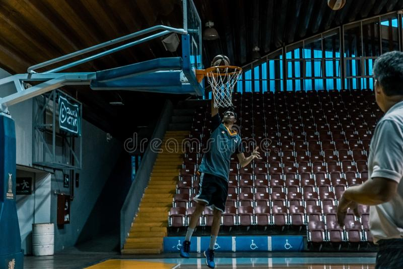 Man in Blue Shirt Trying to Dunk in Basketball Ring stock photos