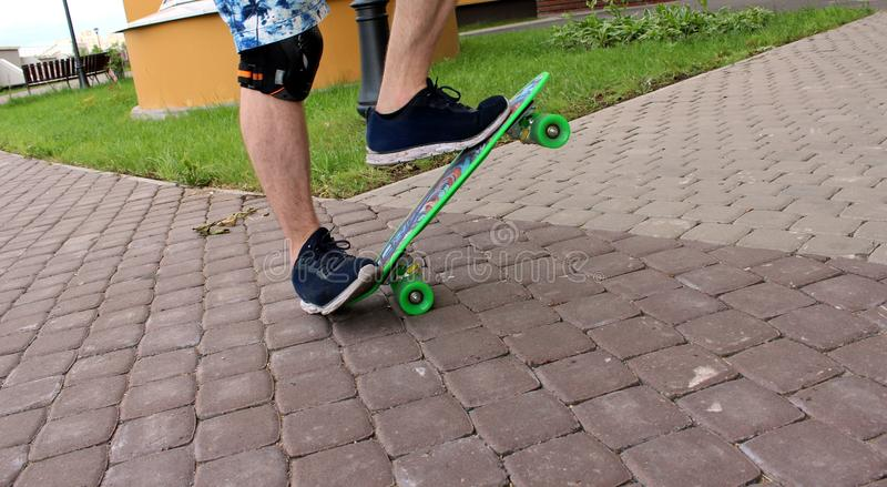 A man in blue sneakers riding a green skateboard stock photography