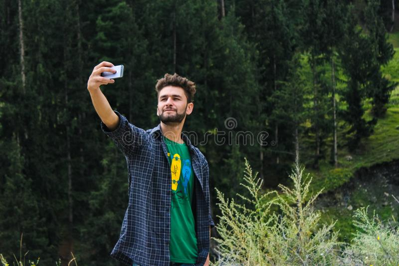 Man in Blue Sports Shirt and Green Top Taking a Selfie Near Green Trees royalty free stock images
