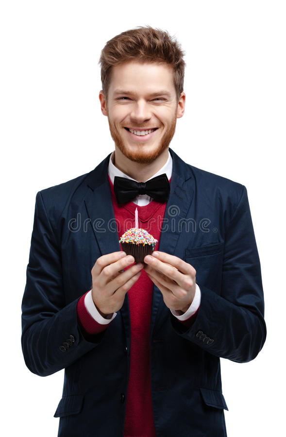 Man in blue suit holds small tart