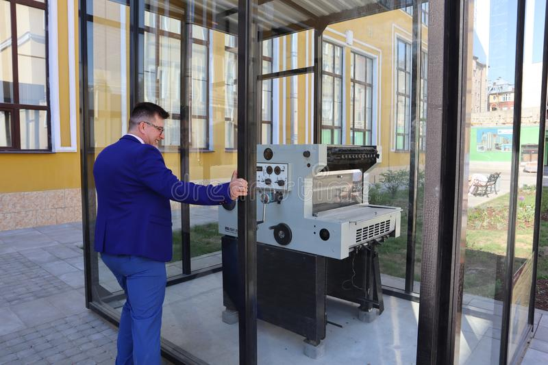 Man in a blue suit looks at the printing press behind the glass royalty free stock photography
