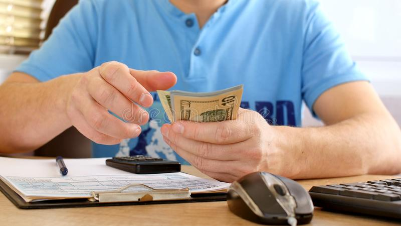 Man in blue T-shirt counting dollars and filling tax form. He calculating expenses and writing on tax document royalty free stock photography