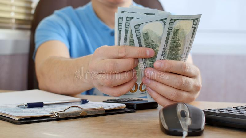 Man in blue T-shirt counting dollars and filling tax form. He calculating expenses and writing on tax document stock photos