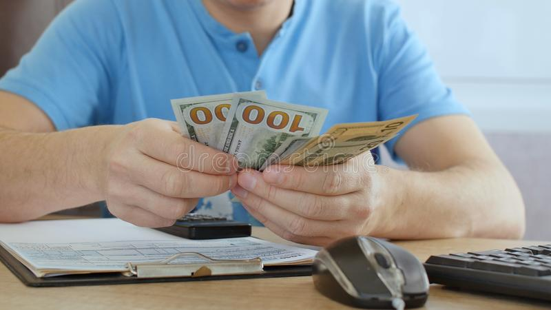 Man in blue T-shirt counting dollars and filling tax form. He calculating expenses and writing on tax document stock image