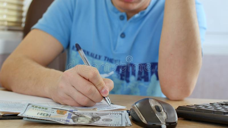 Man in blue T-shirt counting dollars and filling tax form. He calculating expenses and writing on tax document royalty free stock photos