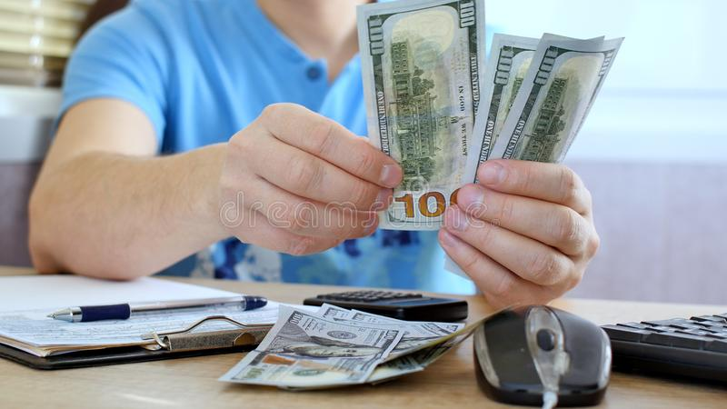 Man in blue T-shirt counting dollars and filling tax form. He calculating expenses and writing on tax document stock photo