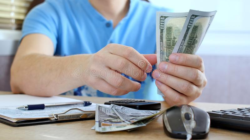 Man in blue T-shirt counting dollars and filling tax form. He calculating expenses and writing on tax document stock photography