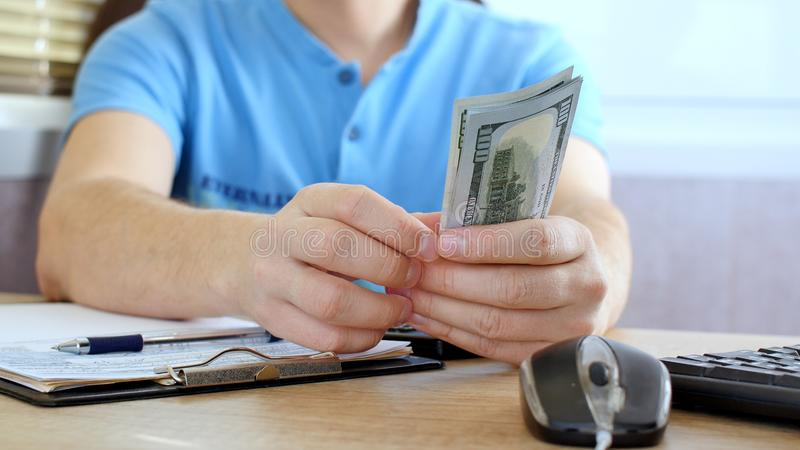 Man in blue T-shirt counting dollars and filling tax form. He calculating expenses and writing on tax document royalty free stock image