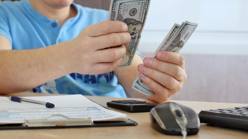 Man in blue T-shirt counting dollars and filling tax form. He calculating expenses and writing on tax document royalty free stock images