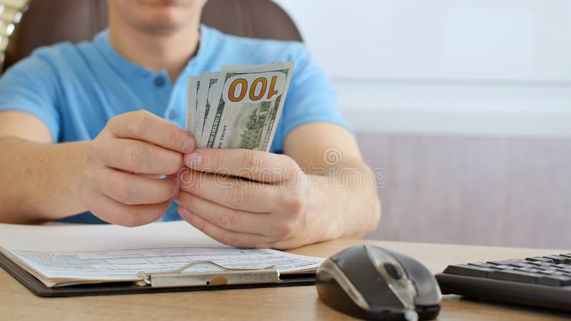 Man in blue T-shirt counting dollars and filling tax form. He calculating expenses and writing on tax document stock images