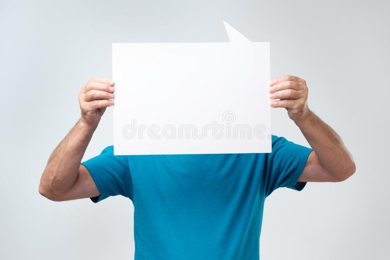 Man in blue t-shirt holding blank copyspace near his face. Faceless man with white poster. royalty free stock photography