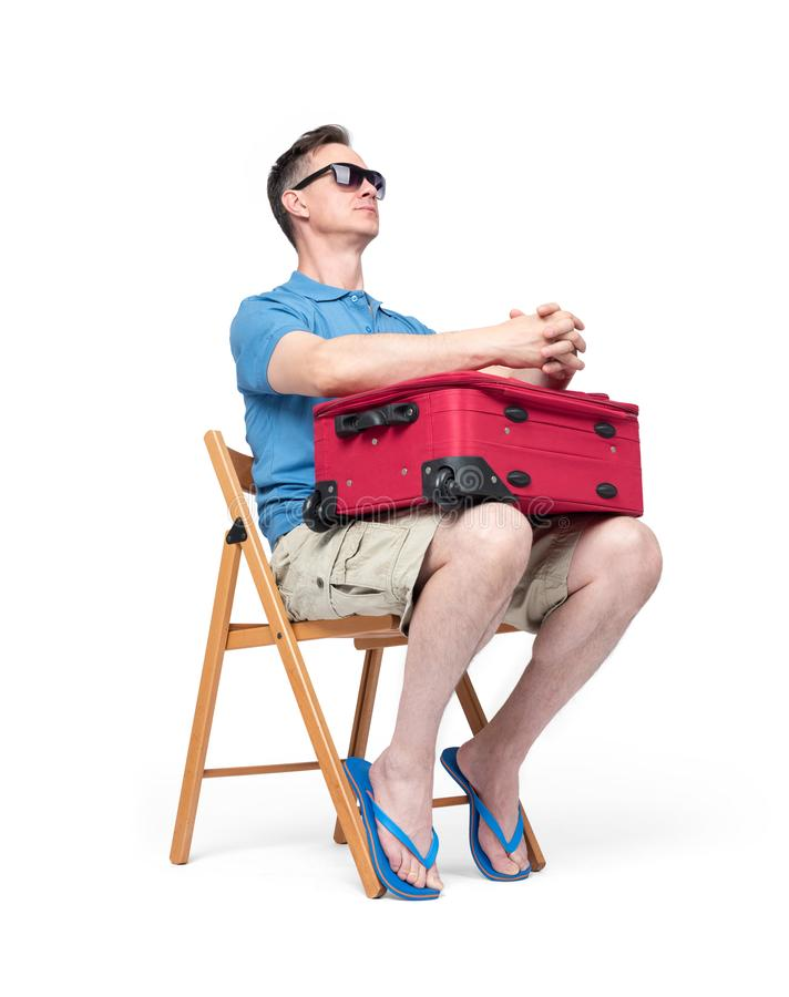 Man in a blue T-shirt, shorts and sunglasses sits on a chair with a red suitcase waiting. Isolated on white background stock photos