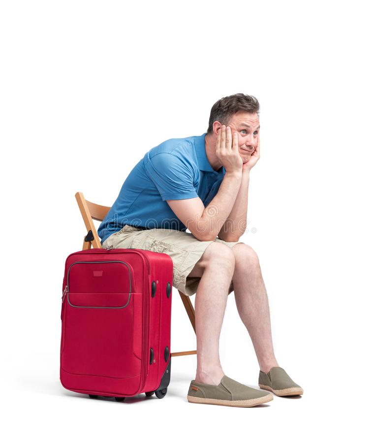 Man in a blue T-shirt and white shorts sits on a chair near a red suitcase, waiting. Isolated on white background royalty free stock photography