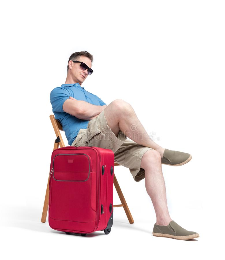Man in a blue T-shirt and white shorts sits on a chair near a red suitcase, waiting. Isolated on white background stock photo