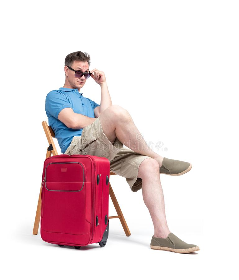 Man in a blue T-shirt and white shorts in sunglasses sits on a chair near a red suitcase, waiting.  on white background royalty free stock photo