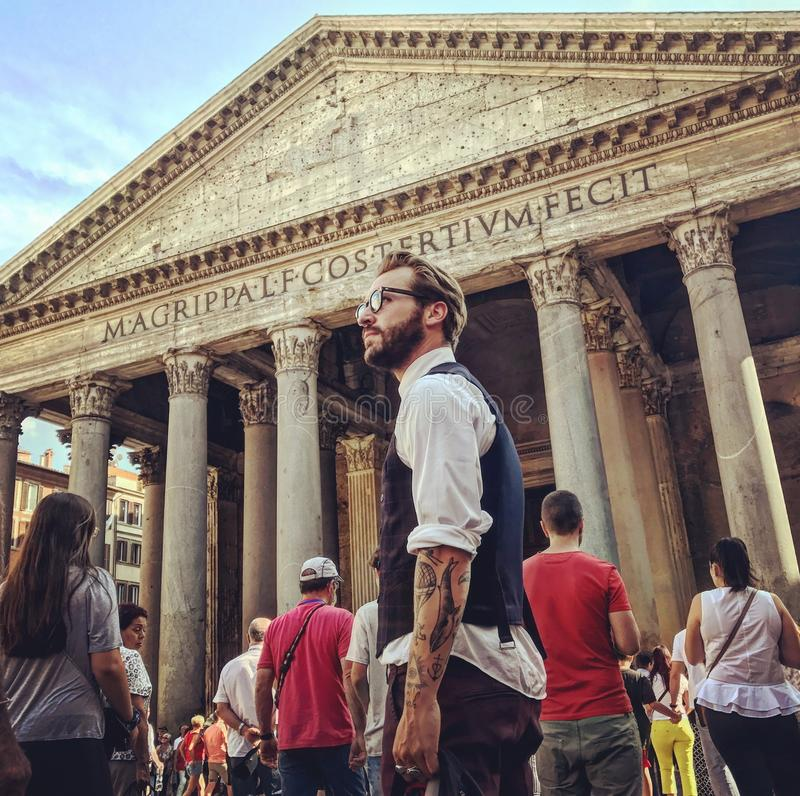Man in Blue Waistcoat and White Dress Shirt Standing Near Magrippa Lf Costertivm Fecit Temple Behind Crowd of People stock images