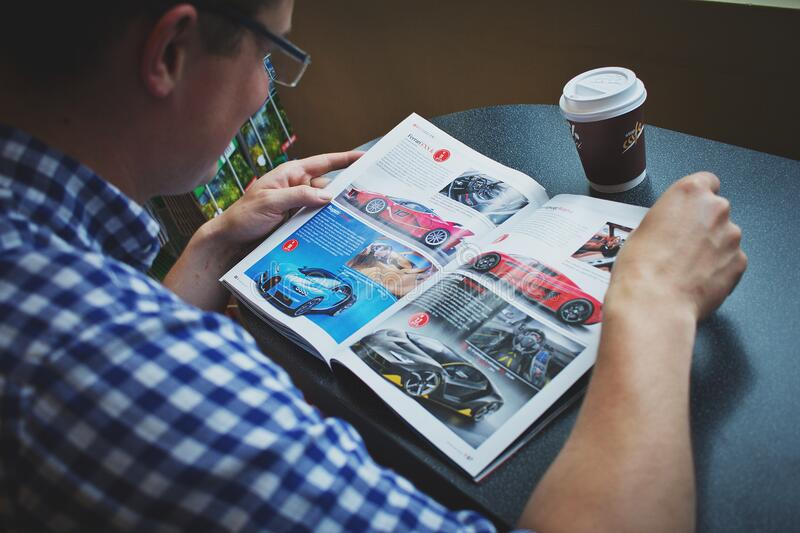 Man in Blue and White Gingham Print Shirt Reading Car Magazine royalty free stock images