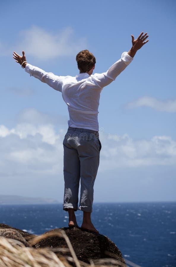 Man on a Bluff above the ocean stock photos