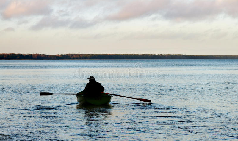 Man on the boat. Silhouette of man in boat on the water royalty free stock photography