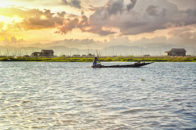 Man in a boat in a Myanmar water body in a sunset. Landscape royalty free stock photo