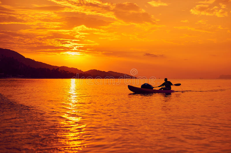 Man on a boat in the sea at sunset.  royalty free stock photos