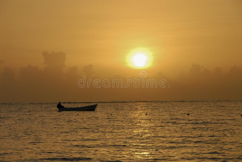 Man in the boat during sunset on Adaman sea. Silhuete of a man sitting in the boat during golden sunset on Adaman sea in Thailand royalty free stock image